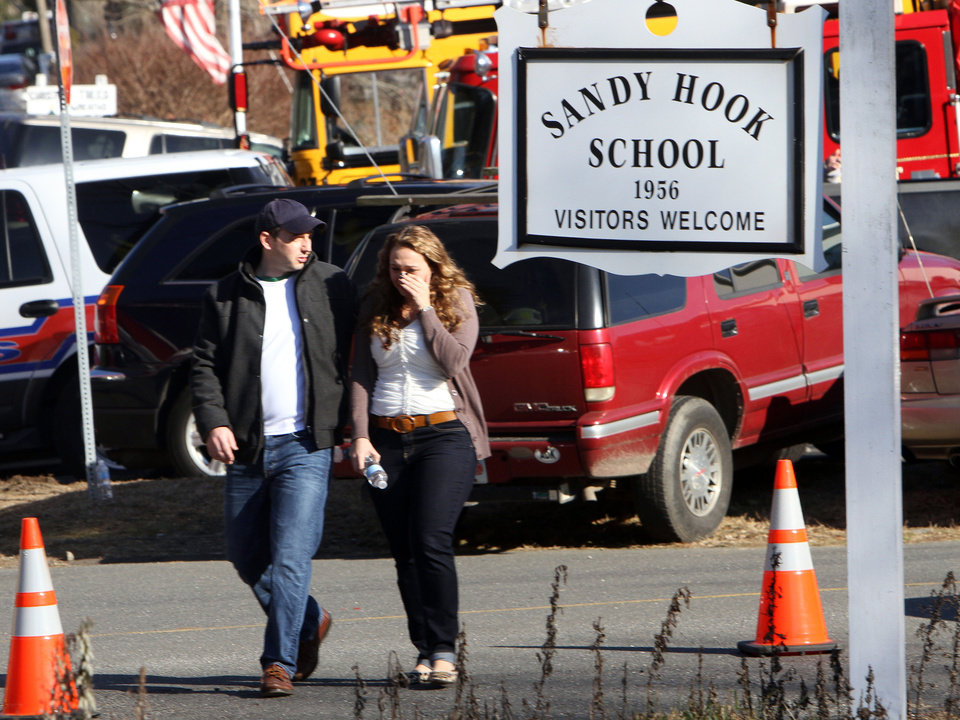 Photo - Parents walk away from the Sandy Hook Elementary School with their children following a shooting at the school, Friday, Dec. 14, 2012 in Newtown, Conn. A man opened fire inside the Connecticut elementary school where his mother worked Friday, killing 26 people, including 20 children, and forcing students to cower in classrooms and then flee with the help of teachers and police. (AP Photo/The Journal News, Frank Becerra Jr.) MANDATORY CREDIT, NYC OUT, NO SALES, TV OUT, NEWSDAY OUT; MAGS OUT ORG XMIT: NYWHI120