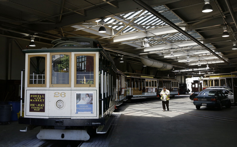 Photo - A worker walks past cable cars not in service at the cable car barn and powerhouse in San Francisco, Tuesday, June 3, 2014. San Francisco's famed cable cars were halted for a second straight day, and the rest of the city's transit system experienced delays after drivers called in sick again on Tuesday, days after overwhelmingly rejecting a new labor contract, officials said. (AP Photo/Jeff Chiu)