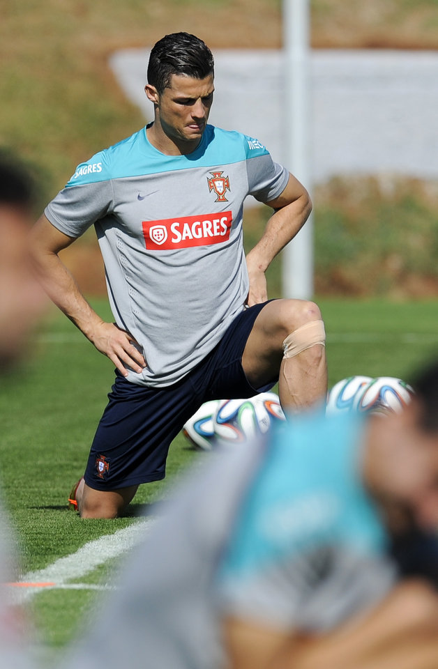 Photo - Portugal's Cristiano Ronaldo uses a small bandage on his left knee as he stretches during a training session of Portugal in Campinas, Brazil, Friday, June 20, 2014. Portugal plays in group G of the Brazil 2014 soccer World Cup. (AP Photo/Paulo Duarte)