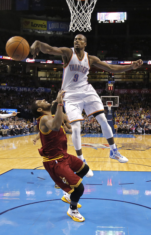 Photo - Oklahoma City's Serge Ibaka (9) blocks a shot by Cleveland's Kyrie Irving (2) during the NBA basketball game between the Oklahoma City Thunder and the Cleveland Cavaliers at the Chesapeake Energy Arena in Oklahoma City, Okla. on Wednesday, Feb. 26, 2014.  Photo by Chris Landsberger, The Oklahoman
