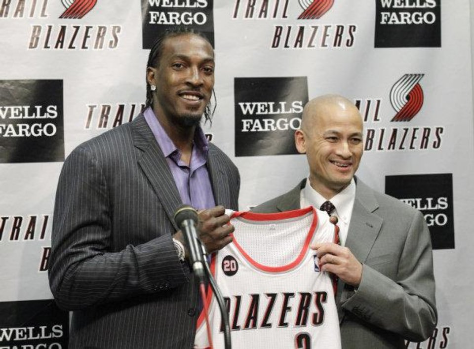 Portland Trail Blazers\' Gerald Wallace, left, smiles as he is introduced by Trail Blazers general manager Rich Cho during a interview before the start of NBA basketball game with the Denver Nuggets Friday, Feb. 25, 2011, in Portland, Ore. Gerald Wallace was acquired from Charlotte in exchange for veteran center Joel Przybilla, second-year forward Dante Cunningham and journeyman center Sean Marks. (AP Photo/Rick Bowmer) Rick Bowmer