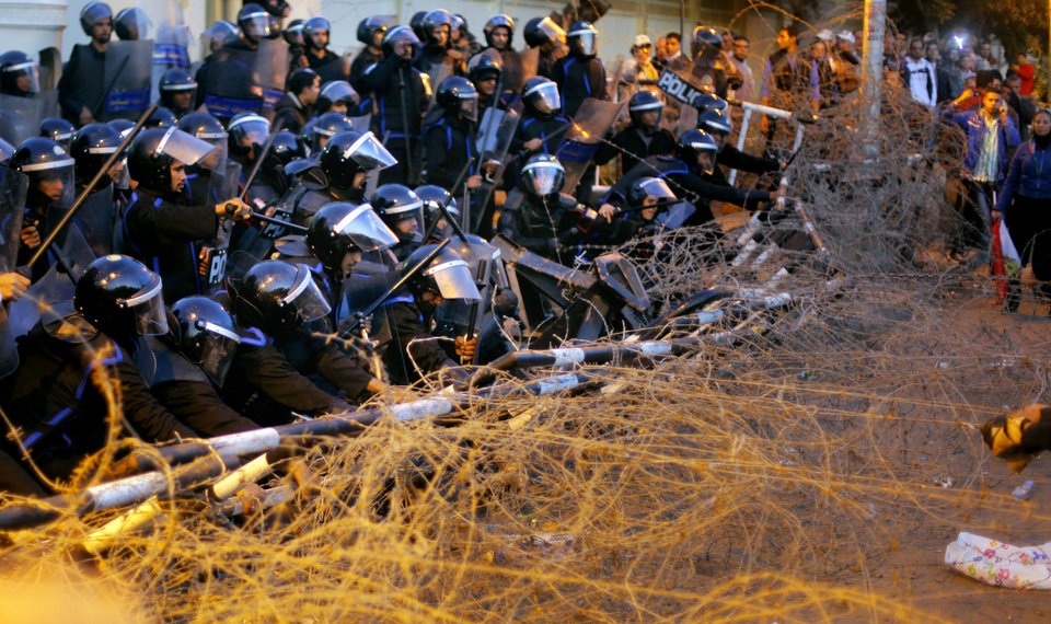 Egyptian anti-riot policemen resist protesters from pulling barbed wire in front of the presidential palace in Cairo, Egypt, Friday, Jan. 25, 2013. Two years after Egypt's revolution began, the country's schism was on display Friday as the mainly liberal and secular opposition held rallies saying the goals of the pro-democracy uprising have not been met and denouncing Islamist President Mohammed Morsi. (AP Photo/Amr Nabil) ORG XMIT: AMR118