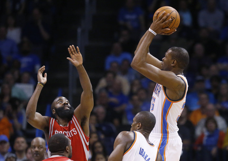 Photo - Oklahoma City Thunder forward Kevin Durant (35) shoots over Houston Rockets guard James Harden (13) during the second quarter of an NBA basketball game in Oklahoma City, Tuesday, March 11, 2014. Oklahoma City won 106-98. (AP Photo/Sue Ogrocki)