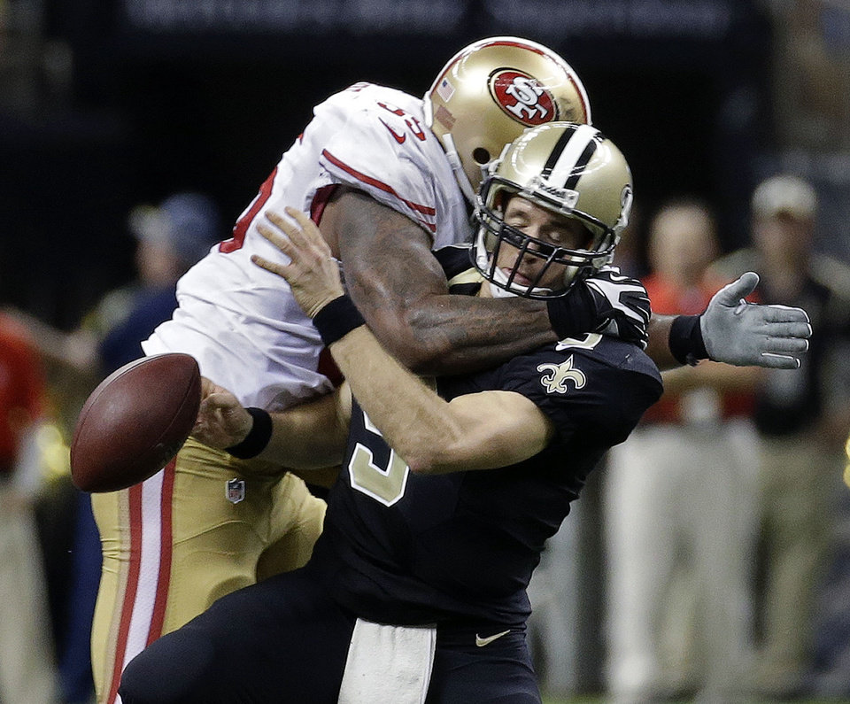 Photo - New Orleans Saints quarterback Drew Brees (9) is sacked by San Francisco 49ers outside linebacker Ahmad Brooks (55) in the second half of an NFL football game in New Orleans, Sunday, Nov. 17, 2013. (AP Photo/Dave Martin)