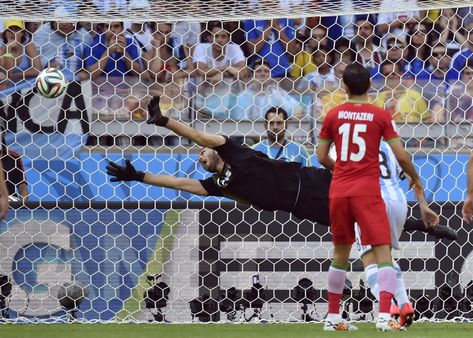 Photo - Iran's goalkeeper Alireza Haghighi dives but fails to stop a goal by Argentina's Lionel Messi during the group F World Cup soccer match between Argentina and Iran at the Mineirao Stadium in Belo Horizonte, Brazil, Saturday, June 21, 2014. Argentina defeated Iran 1-0. (AP Photo/Martin Meissner)