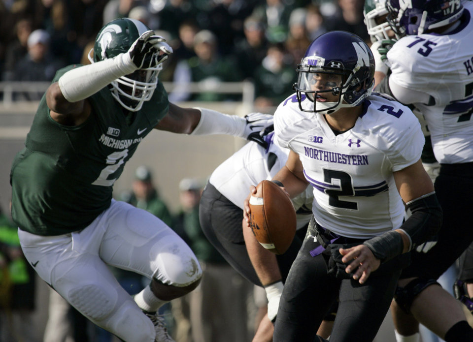 Photo -   Northwestern quarterback Kain Colter, right, scrambles against Michigan State's William Gholston during the first quarter of an NCAA college football game, Saturday, Nov. 17, 2012, in East Lansing, Mich. (AP Photo/Al Goldis)