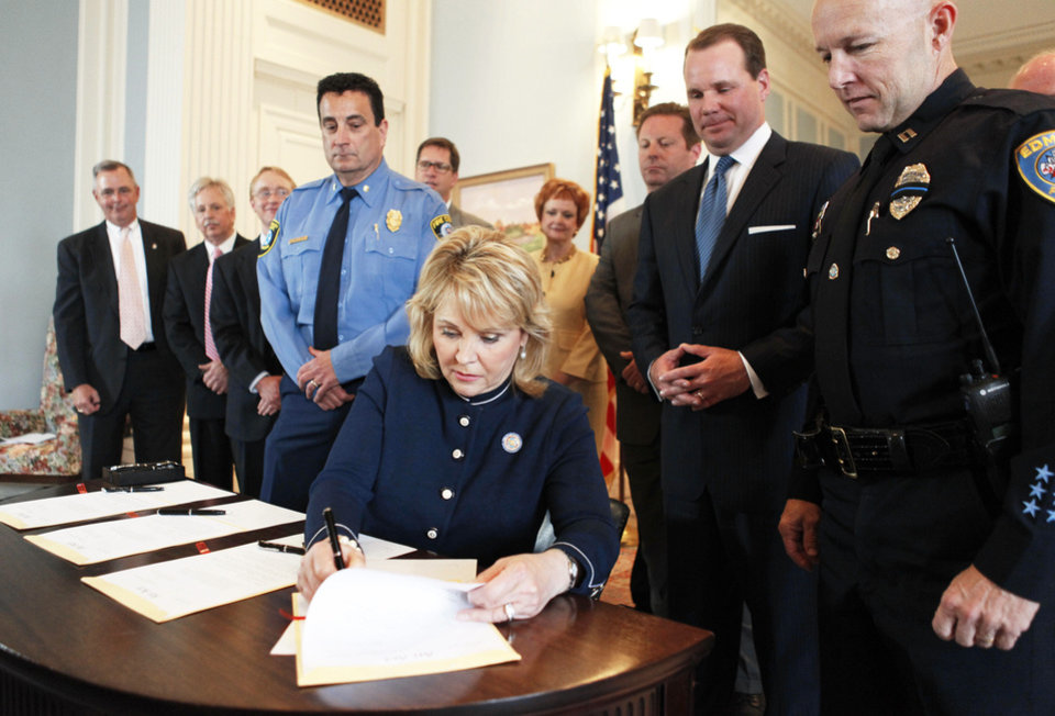 Gov. Mary Fallin signs four school safety bills Tuesday during a signing ceremony in the Blue Room of the state Capitol in Oklahoma City. Photo by Paul Hellstern,  The Oklahoman