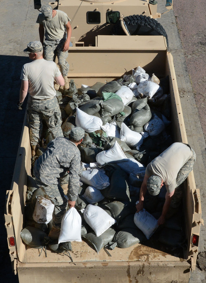 Photo - South Dakota National Guard soldiers load sandbags from a levee across Interstate 29 that blocked traffic between Iowa and South Dakota, Friday, June 20, 2014, in North Sioux City, S.D. The National Weather Service says the Big Sioux River where Iowa, Nebraska and South Dakota meet, already crested at a level lower than expected. (AP Photo/Dirk Lammers)