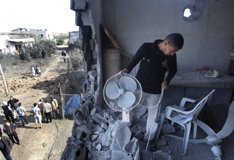 Photo -   A Palestinian man inspects the damage to a mosque after an Israeli airstrike in Beit Hanoun, north Gaza, Friday, Nov. 16, 2012. Israel offered to suspend its offensive in the Gaza Strip on Friday during a brief visit by Egypt's premier there if militants refrain from firing rockets at Israel, an official said, but the Palestinians unleashed a fresh salvo. (AP Photo/Hatem Moussa)