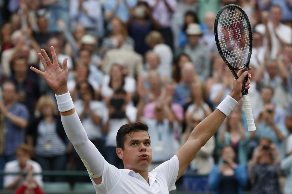 Photo - Milos Raonic of Canada puts his arms aloft as he celebrates defeating Nick Kyrgios of Australia in their men's singles quarterfinal match at the All England Lawn Tennis Championships in Wimbledon, London, Wednesday, July 2, 2014. (AP Photo/Ben Curtis)