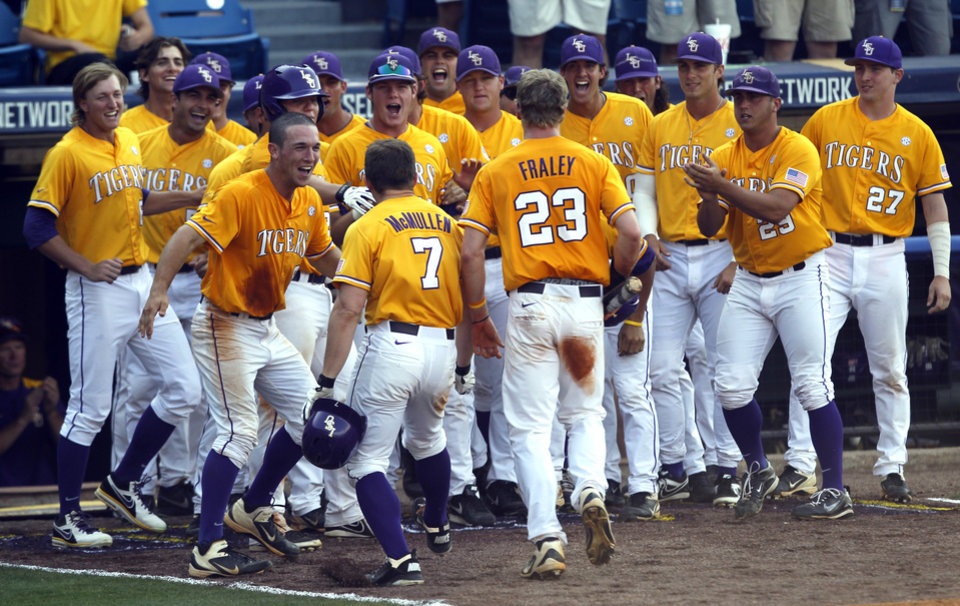 Photo - LSU's Sean McMullen (7) and Jake Fraley  (23) celebrate with teammates after McMullen hit a two-run homer during the eighth inning against Florida during the Southeastern Conference NCAA college baseball tournament on Sunday, May 25, 2014, in Hoover, Ala. (AP Photo/Butch Dill)