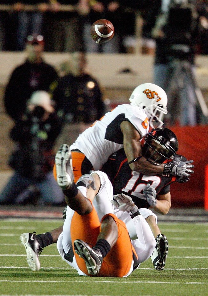 Photo - Eric Morris (12) juggles a pass while defended by Ricky Price (6 top) and Orie Lemon (41) during the first half of the college football game between the Oklahoma State University Cowboys (OSU) and the Texas Tech Red Raiders at Jones AT&T Stadium on Saturday, Nov. 8, 2008, in Lubbock, Tex.  The play was initially ruled a completion, fumble and recovery but the call was overturned after review.By Steve Sisney/The Oklahoman