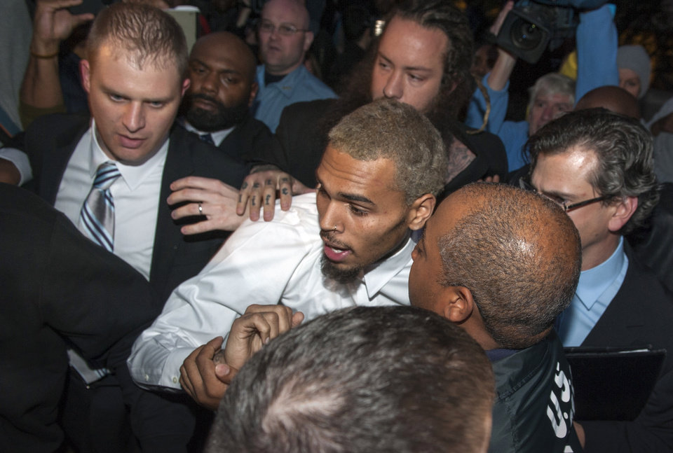 Photo - Singer Chris Brown is surrounded by bodyguards as he departs the H. Carl Moultriel courthouse Monday, Oct. 28, 2013, in Washington. A charge against the Grammy Award-winning R&B singer has been reduced to a misdemeanor and he was ordered released after his arrest Sunday following an altercation outside a Washington hotel. (AP Photo/Cliff Owen)
