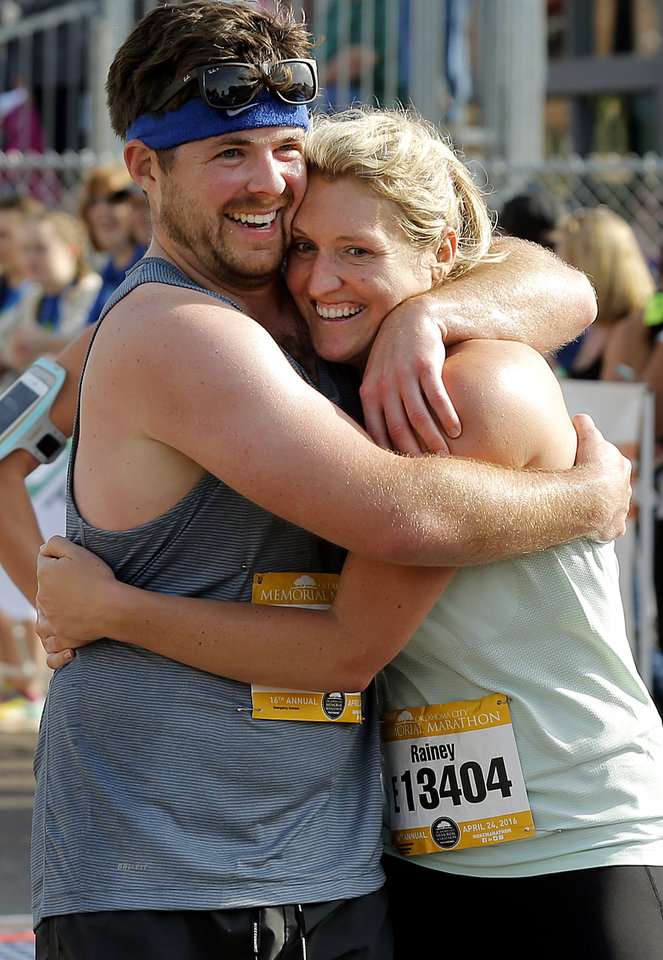 Photo - Michael Cangialosi and Rainey Pittmann celebrate finishing the half marathon with a hug during the Oklahoma Memorial Marathon in Oklahoma City, Okla. on Sunday, April 24, 2016.   Photo by Chris Landsberger, The Oklahoman