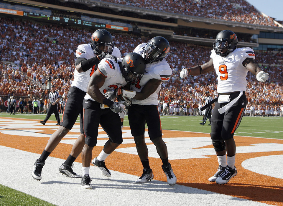 Photo - OSU celebrates a Oklahoma State's Jeremy Smith (31) touchdown during first half of a college football game between the Oklahoma State University Cowboys (OSU) and the University of Texas Longhorns (UT) at Darrell K Royal-Texas Memorial Stadium in Austin, Texas, Saturday, Oct. 15, 2011. Photo by Sarah Phipps, The Oklahoman