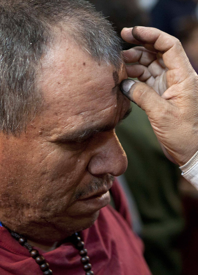 A priest marks a cross using ashes on the forehead of a man, to signify repentance, during Ash Wednesday services at the Metropolitan Cathedral in Mexico City, Wednesday Feb. 22, 2012. Ash Wednesday for Christians worldwide ushers in a period of penitence and reflection, known as the season of Lent, that leads up to Easter Sunday. (AP Photo/Eduardo Verdugo)