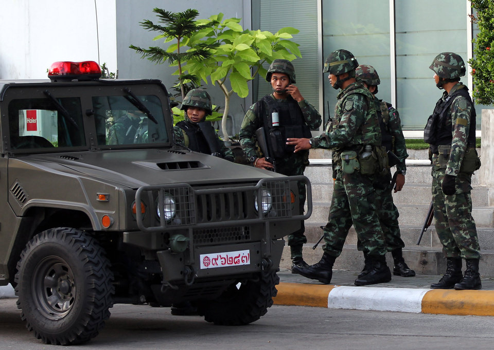 Photo - Thai soldiers gather after arriving outside the National Broadcasting Services of Thailand (NBT) building Tuesday, May 20, 2014 in Bangkok, Thailand. Thailand's army declared martial law in a surprise announcement in Bangkok before dawn on Tuesday, intensifying the turbulent nation's deepening political crisis. The military, however, denied a coup d'etat was underway. (AP Photo/Apichart Weerawong)