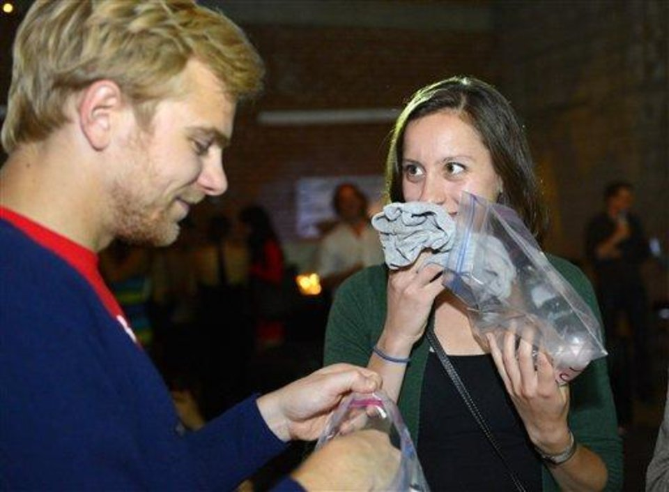 Photo - Konstantin Bakhurin, left, and Martina Desalvo smell shirts during a pheromone party, Friday, June 15, 2012, in Los Angeles. The get-togethers, which have been held in New York and Los Angeles and are planned for other cities, require guests to submit a slept-in T-shirt that will be sniffed by other participants. Then you can pick your partner based on scent. (AP Photo/Mark J. Terrill)