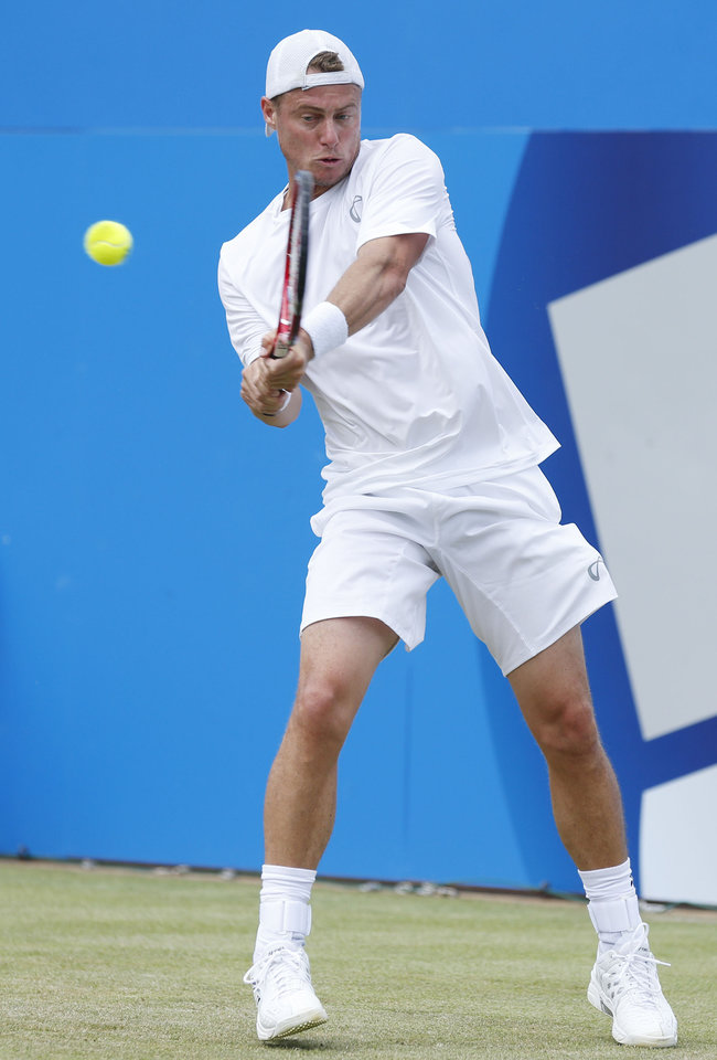 Photo - Australia's Lleyton Hewitt  plays a return to Spain's Feliciano Lopez at The Queen's Club, grass-court tournament  in London Wednesday June 11, 2014. Lopez defeat Hewitt  6-3, 6-4.  (AP Photo/Jonathan Brady/PA) UNITED KINGDOM OUT