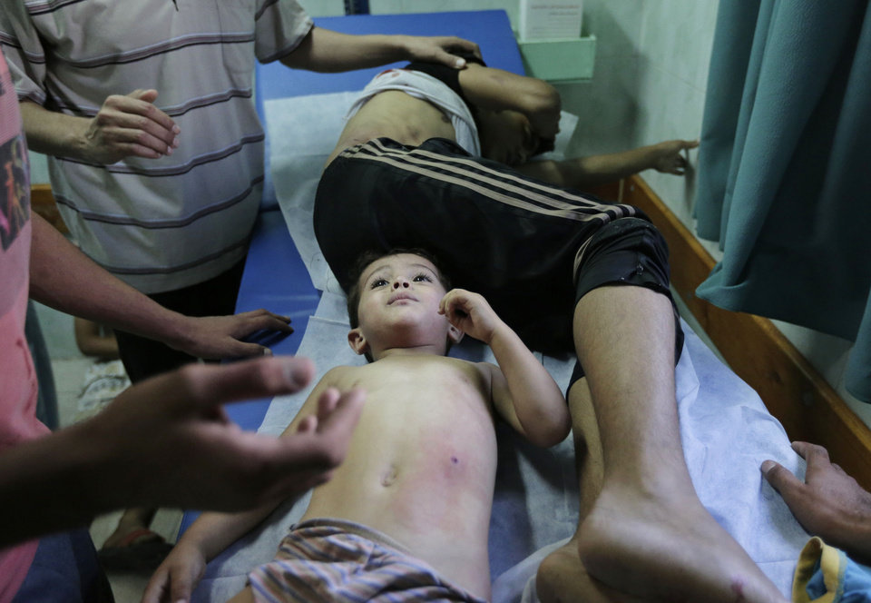 Photo - Palestinians, wounded in an Israeli strike at a house in Beit Lahiya, northern Gaza Strip, receive treatment, at the emergency room of the Kamal Adwan Hospital, in Beit Lahiya, Sunday, Aug. 3, 2014. (AP Photo/Lefteris Pitarakis)