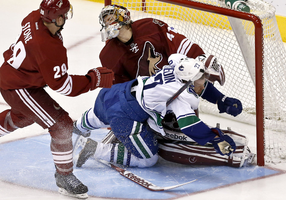 Vancouver Canucks' Daniel Sedin (22), of Sweden, collides with Phoenix Coyotes' Mike Smith as Coyotes' Michael Stone (29) watches during the second period in an NHL hockey game, Thursday, March 21, 2013, in Glendale, Ariz. (AP Photo/Ross D. Franklin)