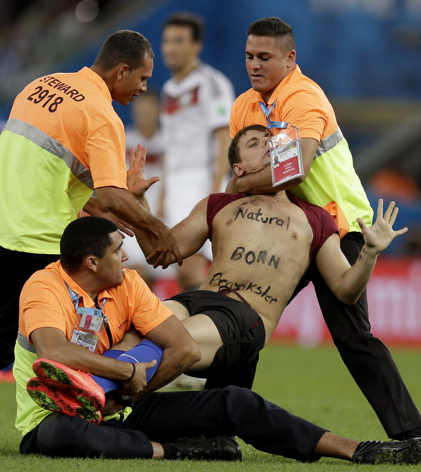 Photo - A spectator who ran on to the pitch during the World Cup final soccer match between Germany and Argentina is subdued by security personnel at the Maracana Stadium in Rio de Janeiro, Brazil, Sunday, July 13, 2014. (AP Photo/Natacha Pisarenko)