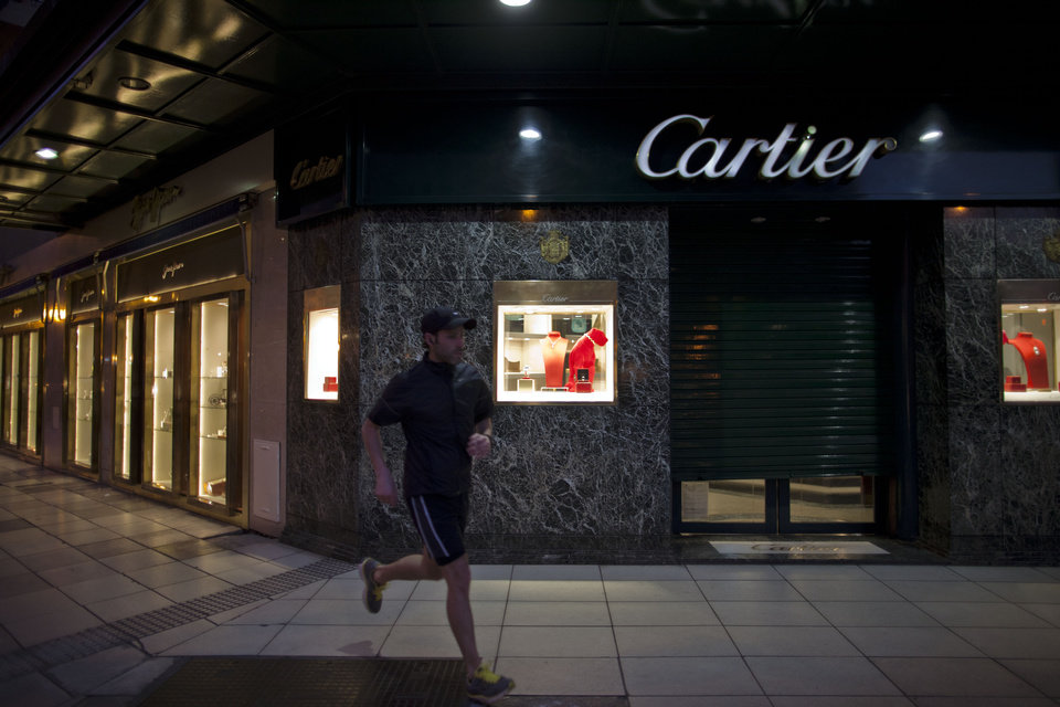 In this Sept. 26, 2012 photo, a man jogs by a Cartier jewelry store along Alvear Avenue in the Recoleta neighborhood in Buenos Aires, Argentina, Wednesday, Sept. 26, 2012. The world's most luxurious designer brands are abandoning Argentina rather than complying with tight new government economic restrictions, leaving empty shelves and storefronts along the capital's elegant Alvear Avenue, where tourists once flocked to see the latest in fashion. (AP Photo/Natacha Pisarenko)