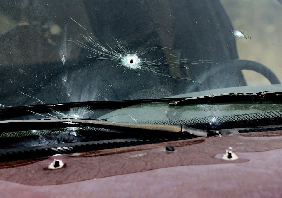 Photo - Several holes can be seen in the windshield and hood of this pickup truck when it was hit by gunfire Sunday night, beginning a crime spree by Michael Dale Vance that spanned multiple counties. Truck is on this property, 920819 S. 3310 Rd., in Lincoln County where Tony Heavner lives. Heavner and two others took shelter behind this truck when Vance began spraying the area with bullets. They were not injured. Vance engaged in a shootout with Wellston police officers, injuring two of them.  He then stole one of the officer's vehicle and continued his crime spree, carjacking a vehicle from a Wellston couple, and then driving to the home in nearby town of Luther where he is believed to have killed the man and woman who lived there. Photo by Jim Beckel, The Oklahoman