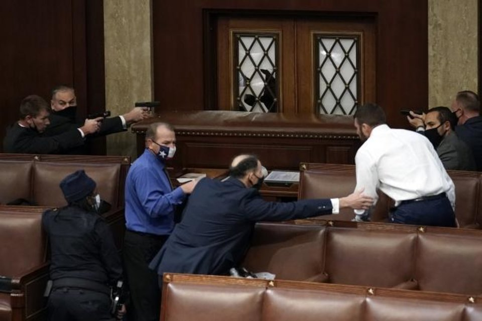 Photo -  U.S. Capitol Police with guns drawn watch as members of a mob try to break into the House Chamber at the U.S. Capitol on Wednesday. Oklahoma Rep. Markwayne Mullen, in white shirt, said he tried to reason with some of the insurgents. [AP Photo]