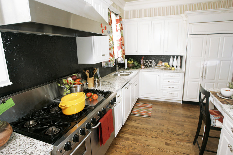 Photo - The show kitchen is modern but with cabinetry and wood flooring that hark back to earlier days.PHOTO BY STEVE GOOCH, THE OKLAHOMAN