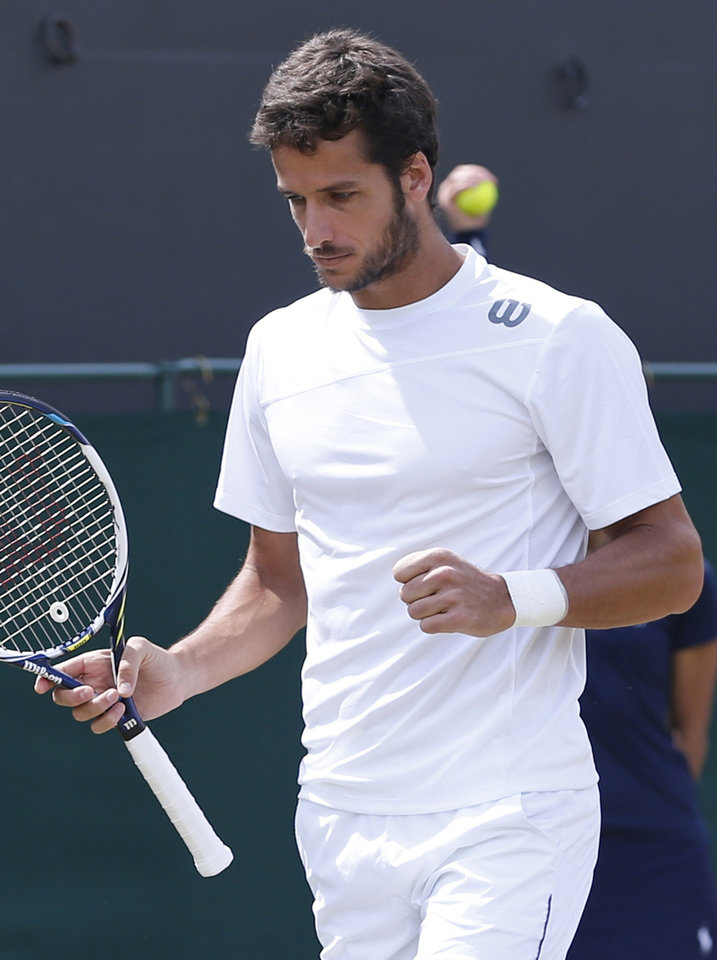 Photo - Feliciano Lopez of Spain celebrates winning a point against John Isner of the U.S. during their men's singles match at the All England Lawn Tennis Championships in Wimbledon, London, Monday, June 30, 2014. (AP Photo/Pavel Golovkin)