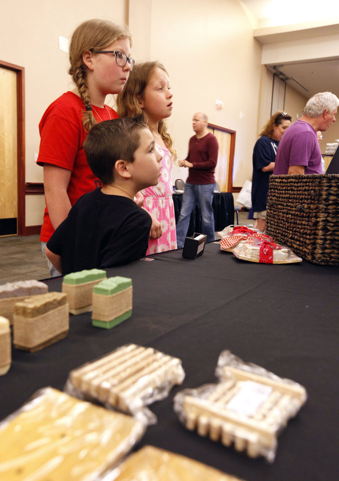 Photo -  Coy Ratcliff, 6, and his sisters Sutton, 11, and Elliott, 8, hear an explanation of the soapmaking process during the Made in Oklahoma Beer, Wine and Food Festival. Photo by Paul Hellstern, The Oklahoman   PAUL HELLSTERN -