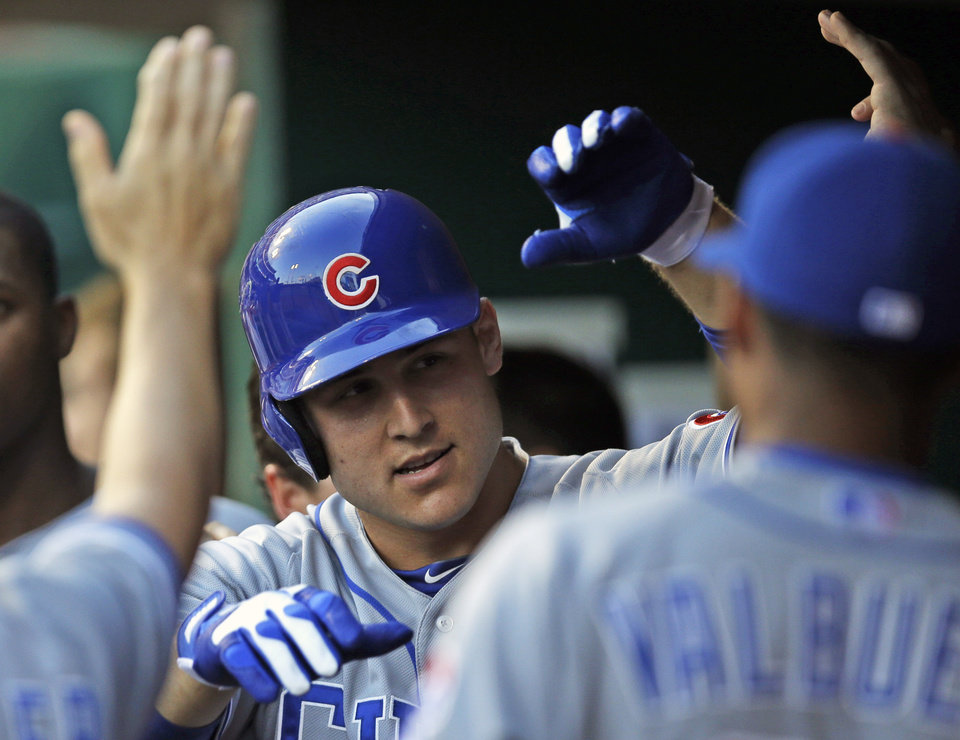 Photo - Chicago Cubs' Anthony Rizzo is congratulated in the dugout after hitting a solo home run off Cincinnati Reds starting pitcher David Holmberg in the third inning of a baseball game, Tuesday, July 8, 2014, in Cincinnati. (AP Photo/Al Behrman)