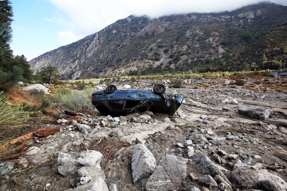 Photo - A car lies where it was swept down a wash in the mountain community of Forest Falls in the San Bernardino Mountains Monday, Aug. 4, 2014. Crews cleared roads in an area where some 2,500 had been stranded after thunderstorms caused mountain mudslides in Southern California over the weekend, while authorities estimated that between six and eight homes were badly damaged and likely uninhabitable. One person was found dead in a vehicle that was caught in a flash flood. A group of campers spent the night at a community center near Forest Falls. (AP Photo/Nick Ut)