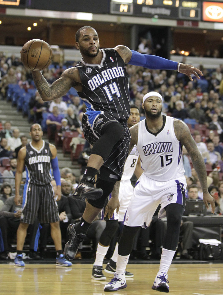 Photo - Orlando Magic guard Jameer Nelson, left, passes off as Sacramento Kings center DeMarcus Cousins, right, looks on during the first quarter of an NBA basketball game in Sacramento, Calif., Friday, Jan. 10, 2014. (AP Photo/Rich Pedroncelli)
