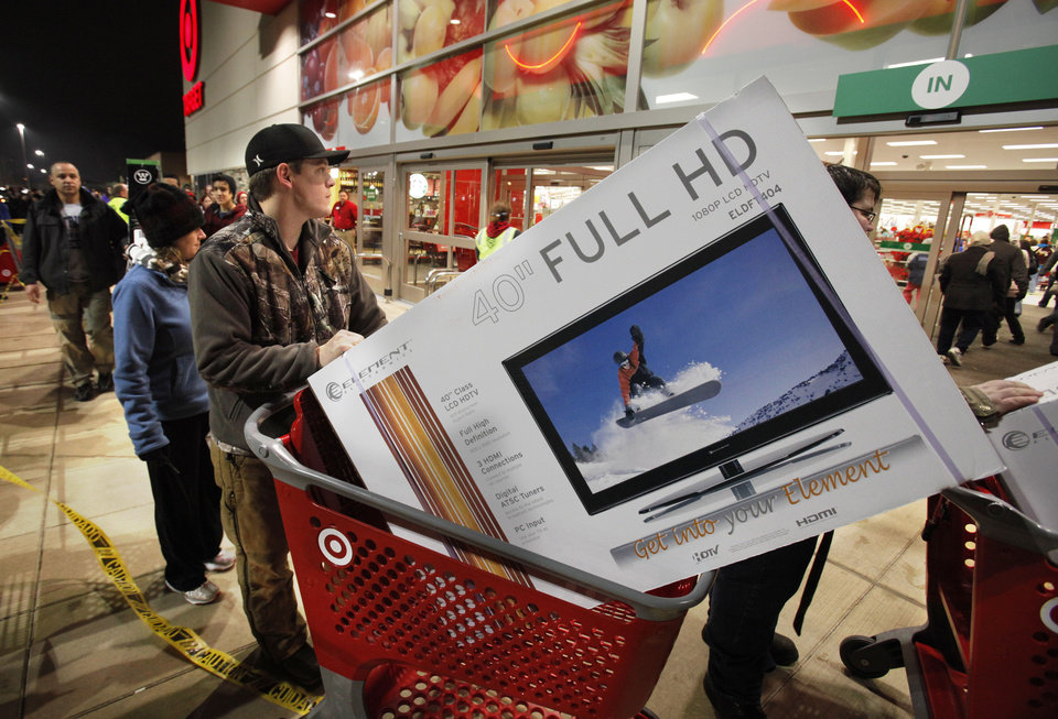 Ryan Martin pushes his door buster purchase from the store in 2011 after Target's midnight opening on Black Friday. Consumers spent an average of $400 during the Black Friday weekend last year. Photo by Steve Sisney, The Oklahoman Archive <strong>STEVE SISNEY - THE OKLAHOMAN</strong>
