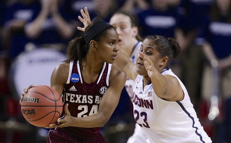Photo - Texas A&M's Jordan Jones (24) is defended by Connecticut's Kaleena Mosqueda-Lewis (23) during the first half of a regional final game in the NCAA college basketball tournament in Lincoln, Neb., Monday, March 31, 2014. (AP Photo/Nati Harnik)