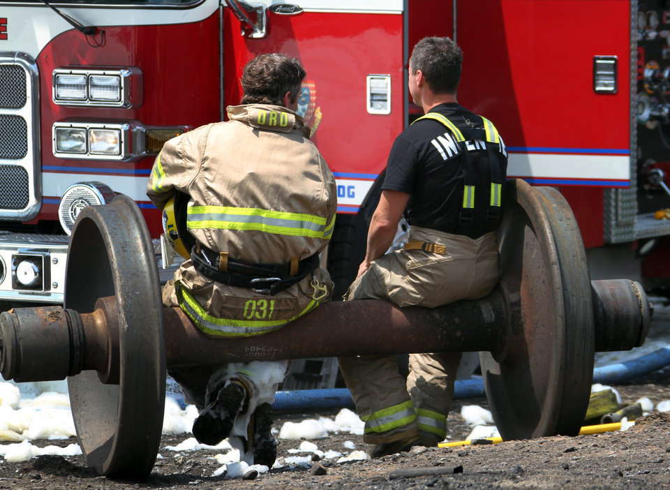 Photo - In a Sunday, July 7, 2013 photo, firefighters take a break on a set of train wheels in Lac-Megantic, Quebec, in a Surete du Quebec handout photo made available Tuesday, July 9, 2013. Thirteen people are confirmed dead and forty more are listed as missing after a train derailed ignited tanker cars carrying crude oil. (AP Photo/Surete du Quebec via The Canadian Press)