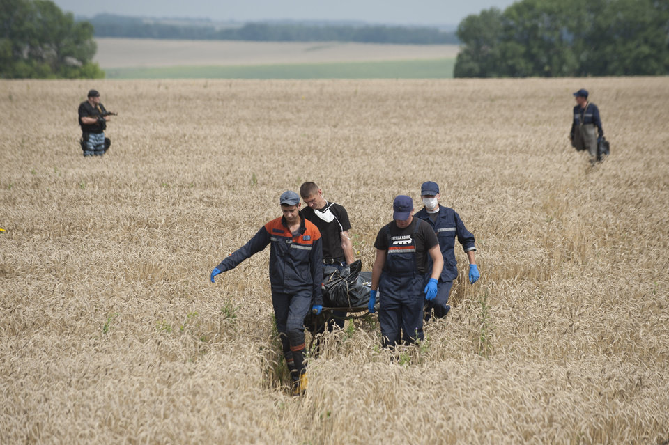Photo - Emergency workers carry the body of a victim at the crash site of a Malaysia Airlines jet near the village of Hrabove, eastern Ukraine, Saturday, July 19, 2014. Ukraine accused Russia on Saturday of helping separatist rebels destroy evidence at the crash site of a Malaysia Airlines plane shot down in rebel-held territory, a charge the rebels have denied. (AP Photo/Evgeniy Maloletka)