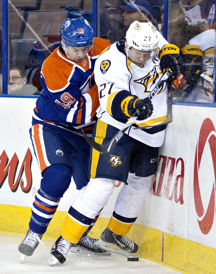 Photo - Nashville Predators Patric Hornqvist (27) is checked by Edmonton Oilers Justin Schultz (19) during first period NHL hockey action in Edmonton, Canada, Sunday, Jan. 26, 2014. (AP Photo/The Canadian Press, Jason Franson)