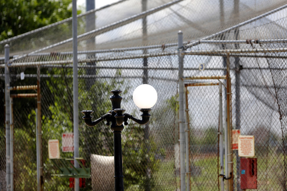 Photo -  Every globe but one is broken on this outdoor lamp along a pathway near the batting cages.    Jim Beckel -  THE OKLAHOMAN