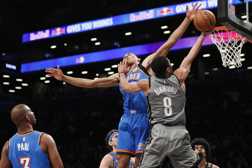 Photo - Brooklyn Nets guard Spencer Dinwiddie (8) collides with Oklahoma City Thunder forward Darius Bazley (7) as he goes up attempting two points during the second half of an NBA basketball game, Tuesday, Jan. 7, 2020, in New York. The Thunder defeated the Nets 111-103 in overtime. (AP Photo/Kathy Willens)