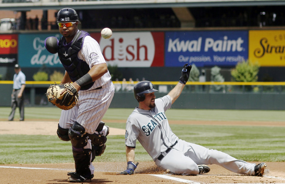 Photo -   Seattle Mariners' Dustin Ackley, right, slides safely across home plate as Colorado Rockies catcher Wilin Rosario watches a bad throw get past him in the first inning of an interleague baseball game in Denver on Sunday, May 20, 2012. (AP Photo/David Zalubowski)
