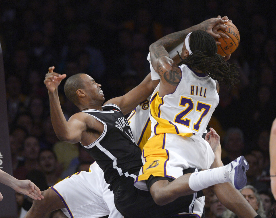 Photo - Los Angeles Lakers forward Jordan Hill, right, tries to put up a shot as Brooklyn Nets center Jason Collins blocks it during the first half of an NBA basketball, Sunday, Feb. 23, 2014, in Los Angeles. (AP Photo/Mark J. Terrill)