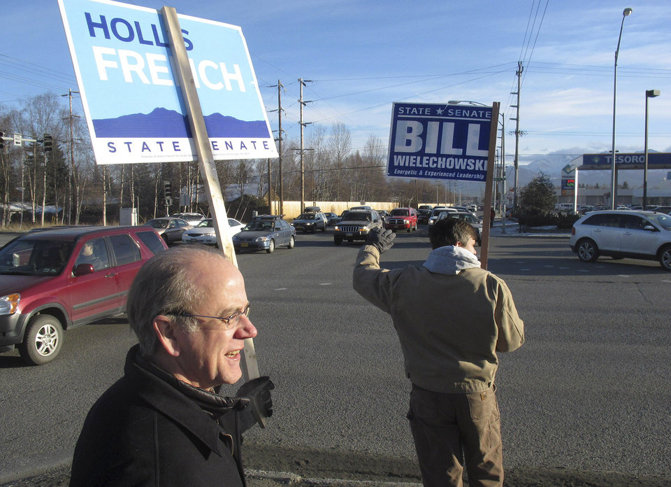 Alaska state Sens. Hollis French, left, and Bill Wielechowski, both Anchorage Democrats, wave signs during a lunch hour rally to support members of the Senate\'s bipartisan coalition. French is being challenged by Republican Bob Bell, while Republican Bob Roses is trying to unseat Wielechowski. (AP Photo/Mark Thiessen)