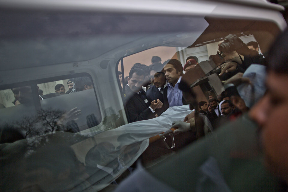 Photo - Pakistani relatives and mourners of a man who was killed in a twin suicide bombing look at the body being taken away from a hospital's morgue, in Islamabad, Pakistan, Monday, March 3, 2014. Two suicide bombers blew themselves up at a court complex in the Pakistani capital on Monday, killing nearly a dozen and wounding scores in a rare terror attack in the heart of Islamabad, officials said. (AP Photo/Muhammed Muheisen)