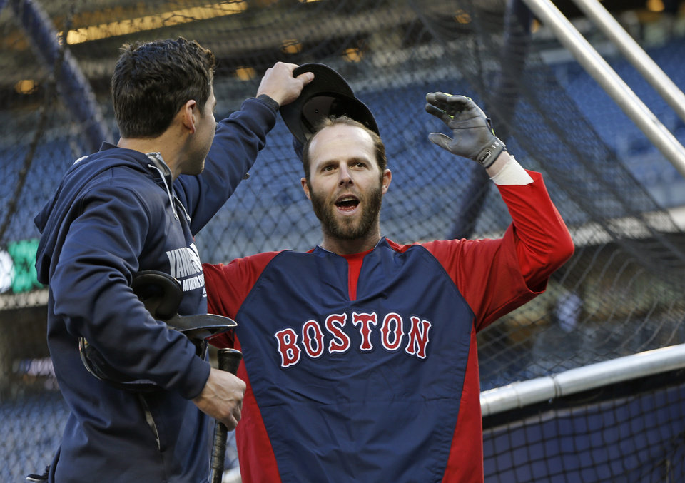 Photo - New York Yankees center fielder Jacoby Ellsbury, left, looks under the cap of Boston Red Sox's Dustin Pedroia after greeting his former teammates during batting practice before a baseball game between the teams at Yankee Stadium in New York, Thursday, April 10, 2014. (AP Photo/Kathy Willens)