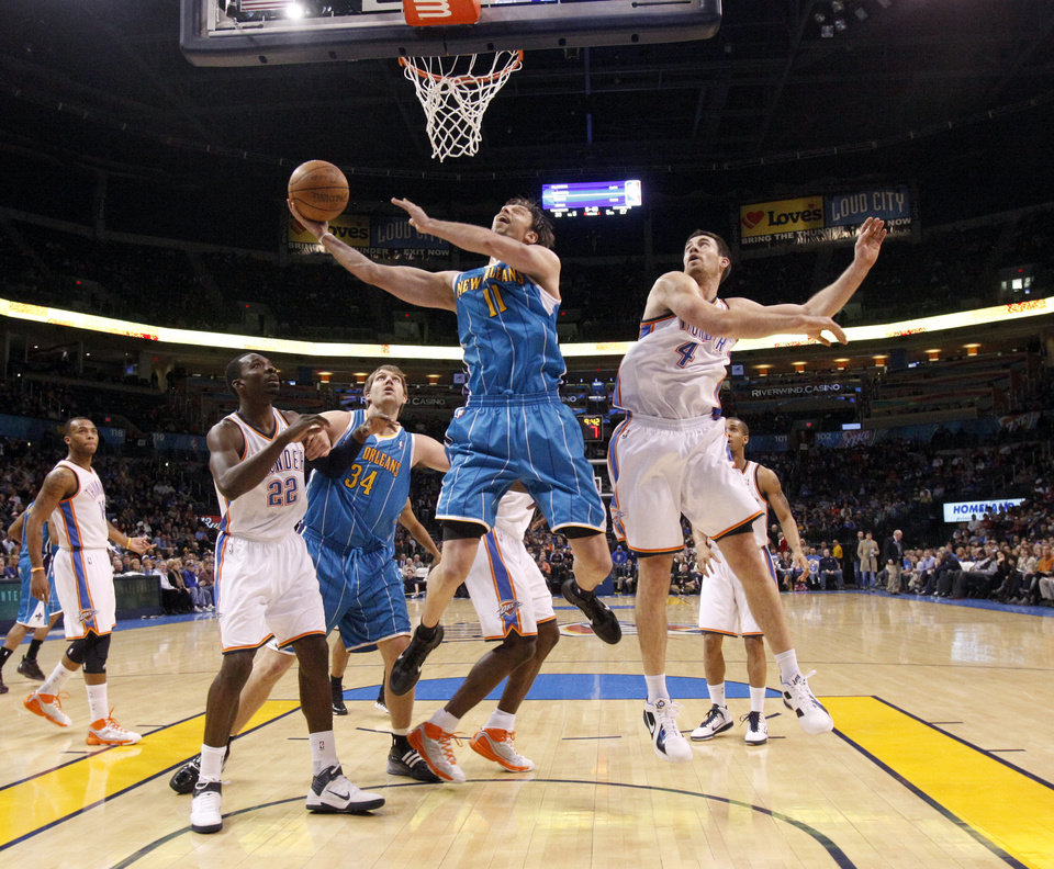 Photo - New Orleans' David Andersen (11) shoots as Oklahoma City's Nick Collison (4) guards him during the NBA basketball game between Oklahoma City Thunder and New Orleans Hornet, Wednesday, Feb. 2, 2011 at the Oklahoma City Arena. Photo by Sarah Phipps, The Oklahoman