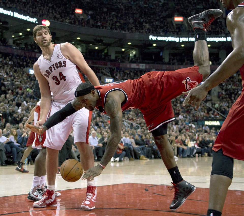 Photo - Miami Heat forward LeBron James, right, falls to the floor after trying to dunk over Toronto Raptors center Aaron Gray, left, during first half NBA basketball action in Toronto on Sunday Feb. 3, 2013. (AP Photo/THE CANADIAN PRESS,Frank Gunn)