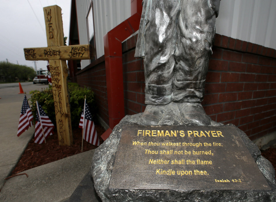 Photo - A statute with the prayer for fire fighters sits in front of a cross outside the volunteer fire department, Thursday, April 17, 2014, in West, Texas, that bears the names of some of those killed one year ago today when a fertilizer plant exploded. (AP Photo/Tony Gutierrez)